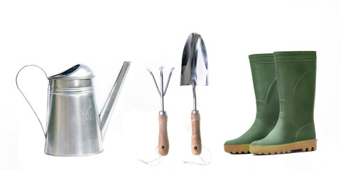 watering can, gardening tools and rubber boots on white background