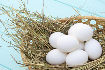 chicken eggs in a basket with hay on a turquoise wooden background. eggs on the hay