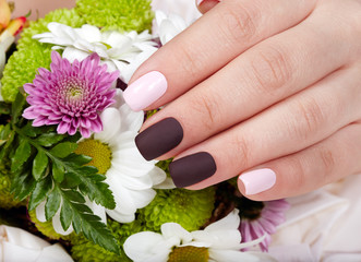 Hand with pink and purple manicured nails and a bouquet of flowers