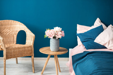 Cozy bedroom fragment of interior with flowers bed and chair on the blue wall background