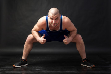 A young athletic man in blue wrestling tights and blue shorts makes a squat with a wide leg arrangement and shows thumbs up on a black isolated background in a photo studio