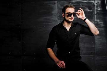 Studio portrait of stylish man wear on black shirt and glasses against steel wall.