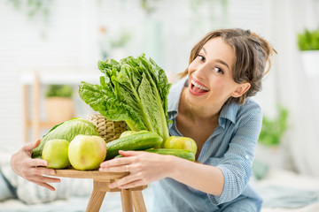 Portrait of a young and beautiful woman sitting with healthy green and fresh food indoors in the bright living room with green plants at home