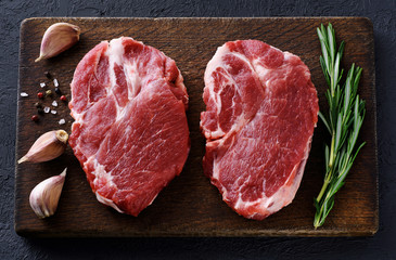 Fresh raw pork steaks, pepper, garlic, salt and rosemary on a dark wooden background.