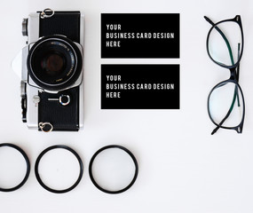 business card mockup with old film camera and lenses with filters and glasses, copy space white background