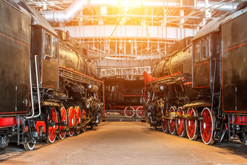 Several locomotives old steam vintage the railroad depot on repair maintenance service.