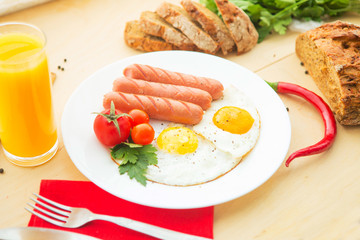 Fried eggs and fried sausage for breakfast.