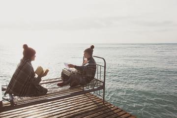 две девушки сидят на старой кровати около моря