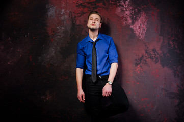 Studio portrait of stylish man, wear on blue shirt and necktie.