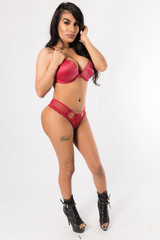 Young fit hispanic woman in red two piece and leather high heels poses on a white background