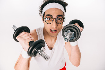 Wall Mural - Portrait of young thin sportsman in eyeglasses holding dumbbells isolated on white