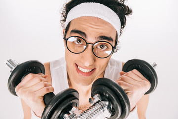 Wall Mural - Young skinny sportsman in eyeglasses holding dumbbells isolated on white