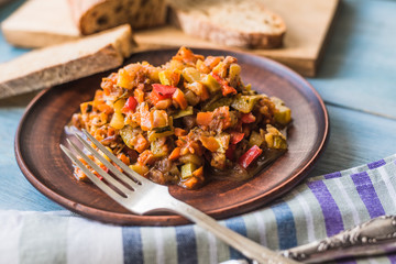 Vegetarian vegetable stew in a plate on a wooden rustic background with sliced bread - top view