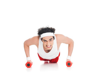 Wall Mural - Skinny sportsman doing push ups with dumbbells isolated on white