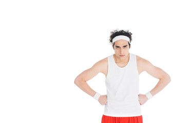 Wall Mural - Thin serious sportsman with hands on waist isolated on white