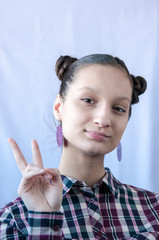 A teenage girl in a checkered shirt shows a victory sign by hand
