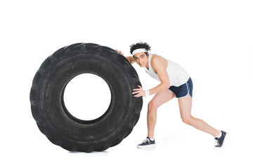 Wall Mural - Young thin sportsman pushing tire of wheel isolated on white