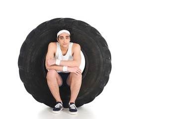 Wall Mural - Young thin sportsman sitting inside tire of wheel isolated on white