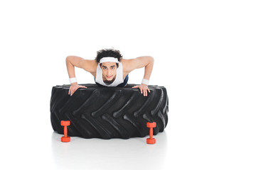 Wall Mural - Young thin sportsman doing push ups on tire of wheel isolated on white