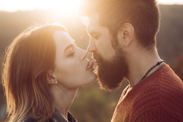 Woman lick with tongue mans lips, close up.