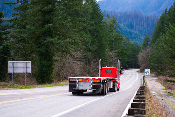 Red big rig semi truck tractor going with empty flat bed semi trailer on the awesome winding road in green forest in Columbia Gorge area