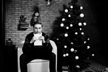 Studio portrait of man with book sitting on chair against christmass tree with decorations.