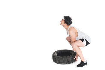Wall Mural - Side view of skinny sportsman raising tire isolated on white