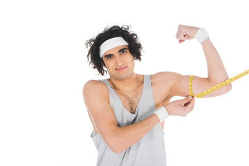 Wall Mural - Young thin sportsman in headband measuring muscles on hand isolated on white