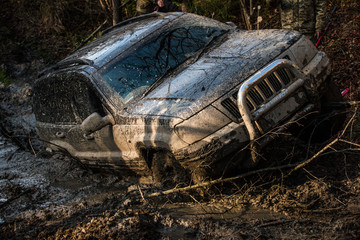 SUV covered with mud on path with deep rut.
