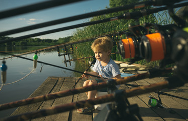 Little baby boy fishing on bank of river with fishing rod