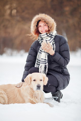 Photo of happy woman in scarf sitting next to labrador at winter