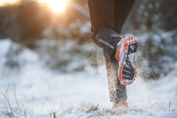 Photo of running man running in sneakers on snowy forest