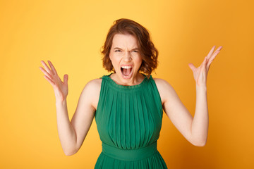 portrait of screaming angry woman isolated on orange