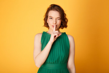 portrait of attractive woman showing silence sign isolated on orange Wall mural