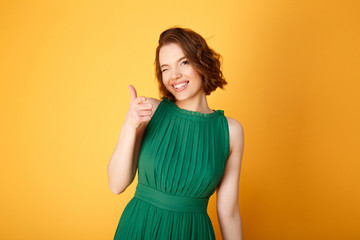 portrait of cheerful woman pointing at camera isolated on orange