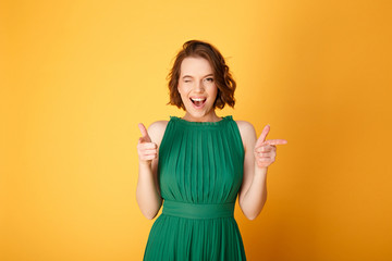 2e75303eec9 portrait of winking woman pointing at camera isolated on orange