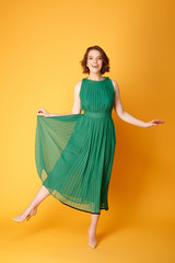 young beautiful woman in green dress posing isolated on orange