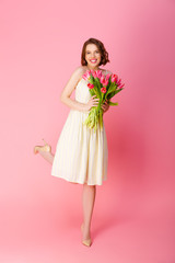 attractive smiling woman with bouquet of spring tulips isolated on pink