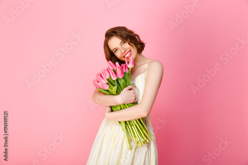 cheerful woman hugging bouquet of pink tulips isolated on pink