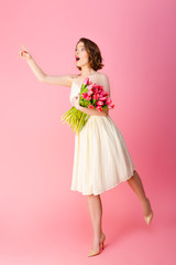 shocked woman with bouquet of pink tulips pointing away isolated on pink