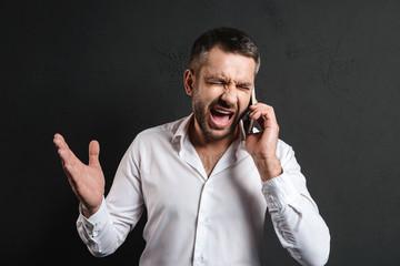 Displeased businessman talking by mobile phone.