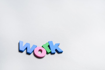 WORK, word written on white background with colorful polystyrene letters.