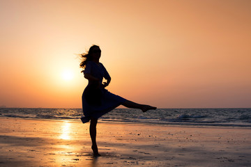 Girl dancing on the beach at sunset