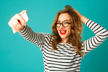 Portrait of young beautiful blond smiley woman making selfie and holding her hair over blue background