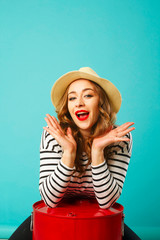 Portrait of young beautiful blond woman in hat with flirting expression on her face over blue background