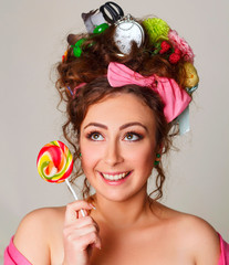 Portrait of young and funny woman with candy in her hands wearing interesting and creative hairstyle