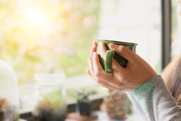 Woman hands holding hot cup of coffee or tea in morning.