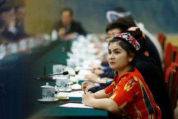 A delegate wearing a traditional costume attends a session of the Xinjiang Uyghur Autonomous Region on the sidelines of the National People's Congress in Beijing