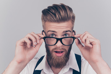Close up portrait of handsome virile masculine emotion expressing groomed classy smart intelligent clever manager with big eyes touching rimmed glasses isolated on gray background