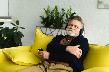 happy senior man in headphones listening music with smartphone at home